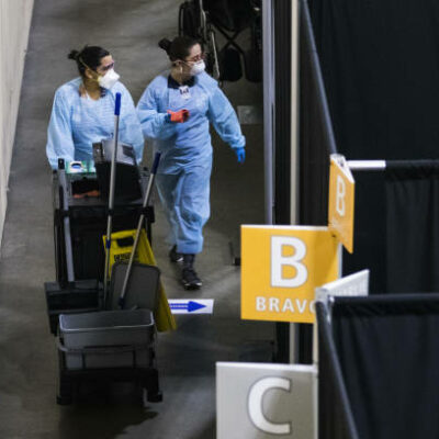 Medical workers wearing protective gear walk through the UMass Memorial Health Care field hospital at the DCU Center in Worcester, Massachusetts, U.S., on Wednesday, April 15, 2020. Covid-19 has infected 2 million people around the world as the new coronavirus marks another grimmilestone. Photographer: Adam Glanzman/Bloomberg via Getty Images