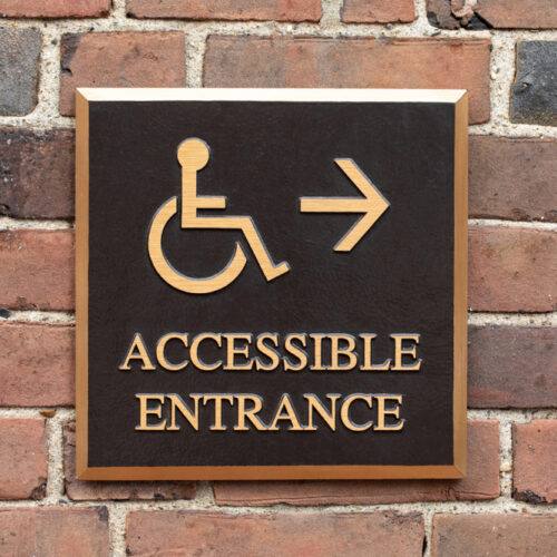 Close up on a bronze wheelchair and handicapped accessible entrance sign, on a brick wall